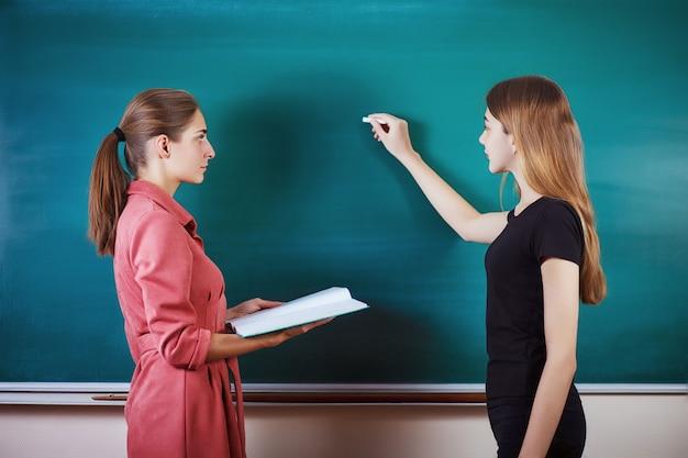 Uczeń z nauczycielem stoi w klasie na tablicy.