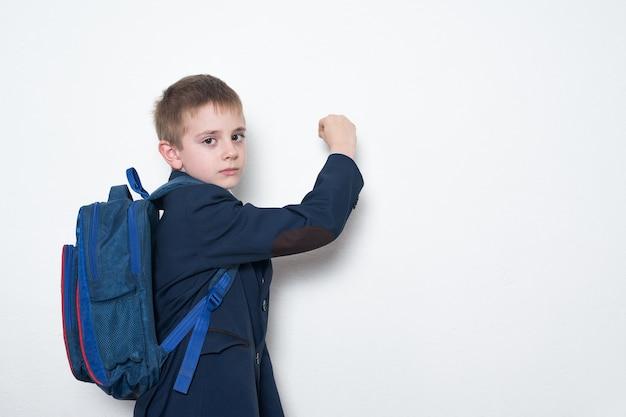 Uczeń z plecakiem pisze na tablicy. gimnazjum. białe tło, miejsce na kopię