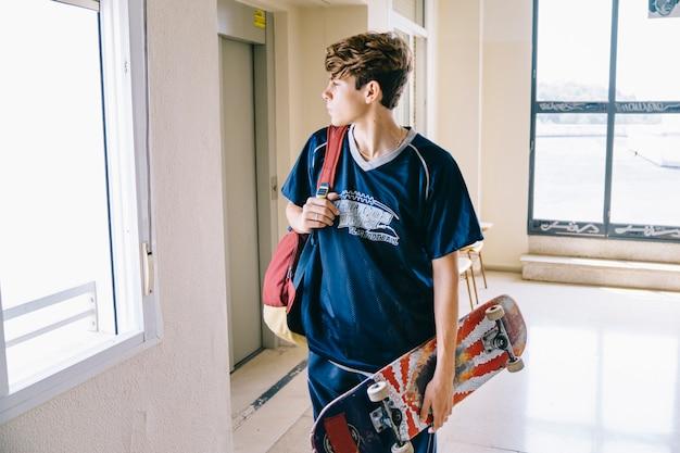 Uczeń z skateboard w budynku