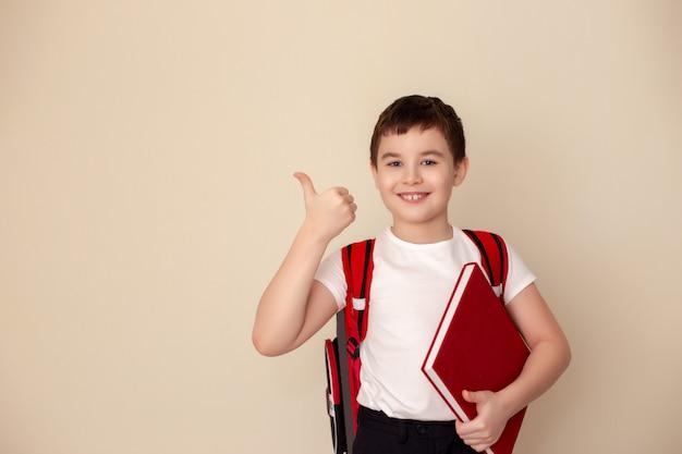 Uczeń z torbą trzyma kciuk w górę.