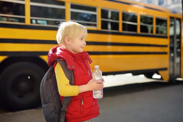 Uczeń z tornistrem i butelką wody w pobliżu żółtego autobusu szkolnego