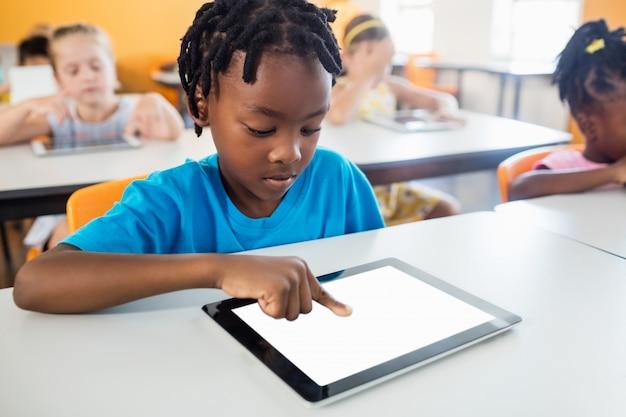 Uczeń za pomocą komputera typu tablet w klasie