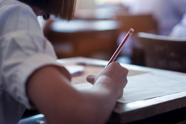 Uczeń zdający egzamin ze stresem w klasie szkolnej