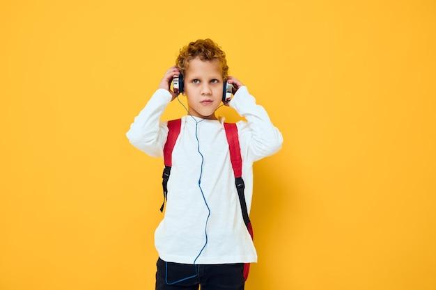 Uczeń ze słuchawkami muzyka czerwony plecak żółte tło