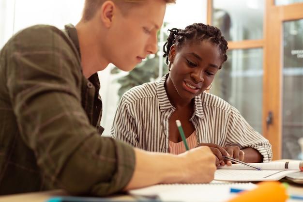 Uczenie się języka. zadowolona afroamerykanka pochyla głowę, kontrolując swojego ucznia