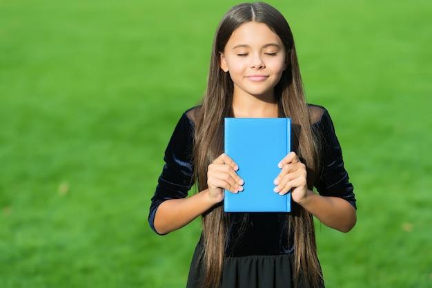 Uczenie się na pamięć. szczęśliwe dziecko uczy się z książki z zamkniętymi oczami. biblioteka szkolna. edukacja czytelnicza. wiedza i informacja. umiejętności uczenia się to nawyki.