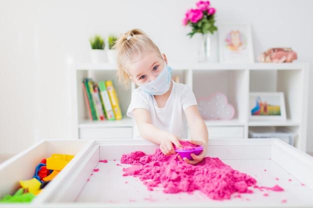 Uczenie się w domu podczas pandemii wirusów. mała dziewczynka bawi się z różowym piaskiem kinetycznym w domu, ubrana w ochronną maseczkę ochronną.