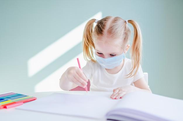 Uczenie się w domu podczas pandemii wirusów. mała dziewczynka rysująca w domu, nosząca chirurgiczne maski na twarz w celu ochrony przed wirusem.