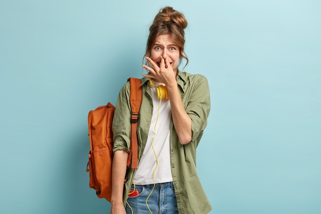 Uczennica czuje smród lub nieprzyjemny zapach podczas studiów, zakrywa nos i ma niezadowoloną mimikę twarzy