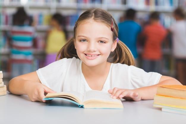 Uczennica czytanie książki w bibliotece