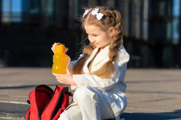 Uczennica dziecko pić świeżą wodę na zewnątrz. mała dziewczynka wyjąć w szkolnym napoju między lekcjami na terenie kampusu. powrót do szkoły. dzieciak zdrowy styl życia.