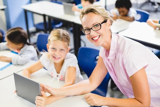 Uczennica i nauczyciel używa cyfrową pastylkę w sala lekcyjnej
