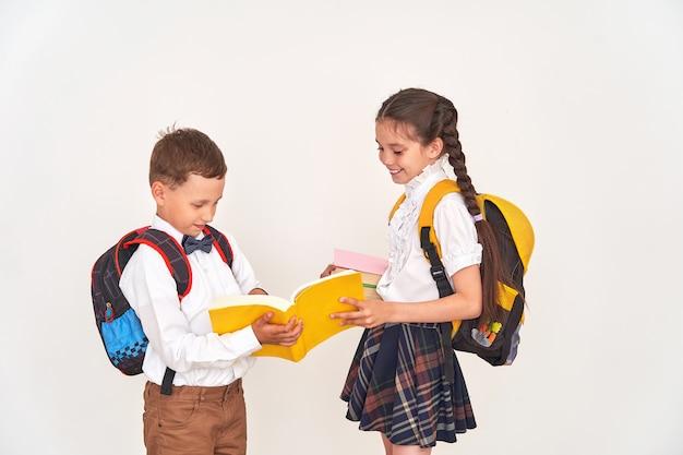 Uczennica i uczeń z plecakami patrzeją książkę na białym tle.