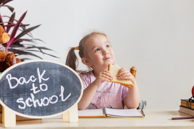Uczennica je kanapkę w przerwie obiadowej po zajęciach