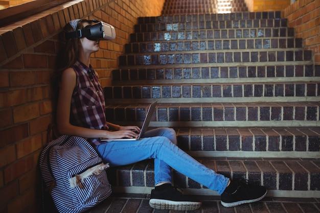 Uczennica korzystająca z zestawu słuchawkowego i laptopa wirtualnej rzeczywistości na klatce schodowej