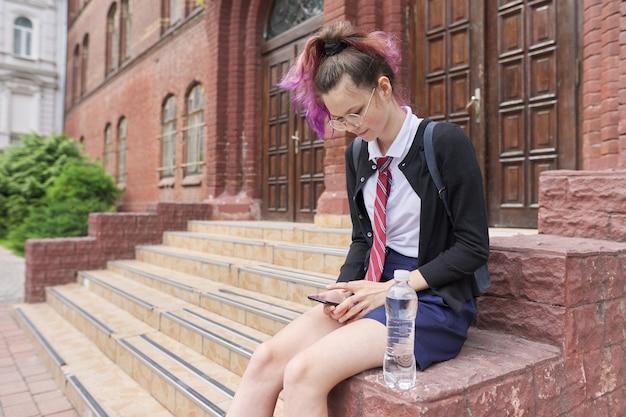 Uczennica nastolatka w mundurze z plecakiem za pomocą smartfona. dziewczyna w pobliżu budynku szkoły, miejsce. powrót do szkoły, powrót na studia, edukacja, koncepcja nastolatków