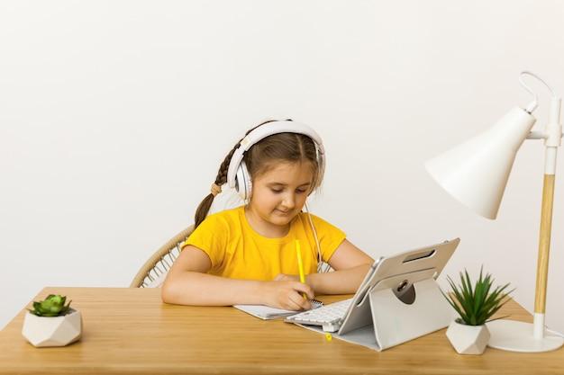 Uczennica nosi słuchawki online i uczy się rozmowy wideo