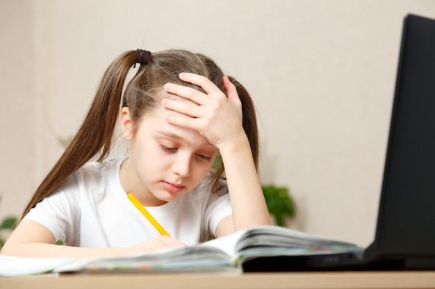 Uczennica odrabia lekcje w domu siedząc przy stole. położyła rękę na głowie, bardzo zmęczona uczeniem się na odległość. izolacja ze względu na zagrożenie zakażeniem koronawirusem