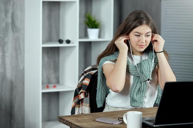 Uczennica odrabia lekcje w domu, wkładając słuchawki do uszu