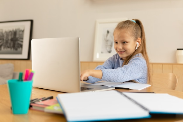 Uczennica patrząc na ekran laptopa i uśmiechnięta.