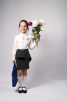 Uczennica pierwszej klasy w białej koszuli z kwiatami i plecakiem