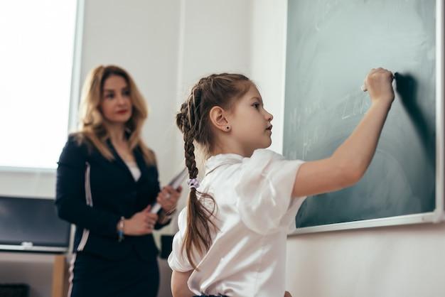 Uczennica pierwszej równiarki pisze na tablicy. lekcja szkolna nauczyciel i uczeń.
