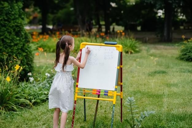 Uczennica pisze lekcje na tablicy i trenuje na świeżym powietrzu