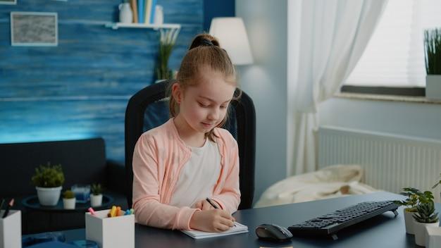 Uczennica pisze na notebooku z piórem do pracy domowej