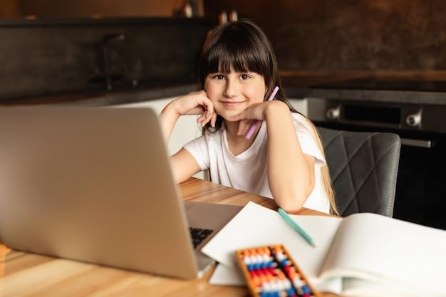 Uczennica po nauce online z laptopem. dziewczyna studiuje i odrabia lekcje w domu podczas rozmowy wideo. kształcenie na odległość