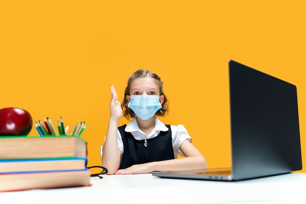 Uczennica podnosząca rękę i siedząca przy laptopie w masce na żółtym tle nauka na odległość
