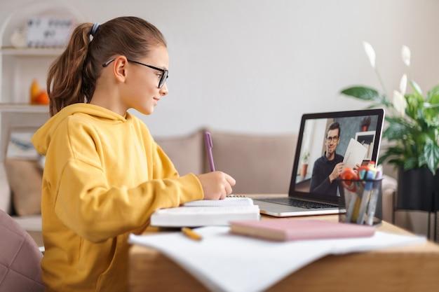 Uczennica prowadząca wideokonferencję z nauczycielem online na laptopie w salonie w domu