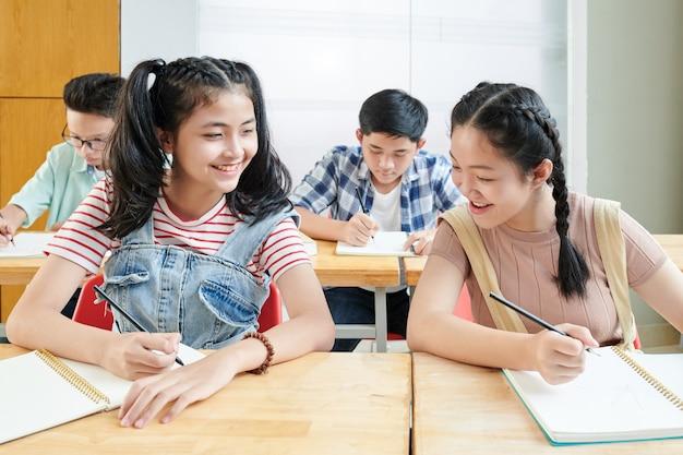 Uczennica przeglądająca zeszyt swojej koleżanki z klasy i próbująca przepisać jej odpowiedzi testowe