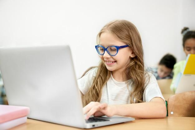 Uczennica przy biurkiem w klasie pracuje w laptopie.