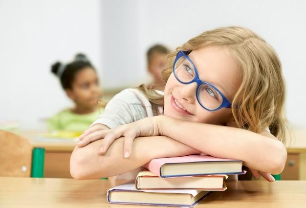 Uczennica przy biurku, opierając się na książkach, odwracając wzrok.
