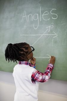 Uczennica robi matematyki na tablicy w klasie