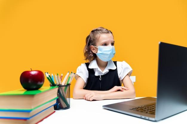 Uczennica siedząca przy laptopie w masce ucząca się online na żółtym tle nauka na odległość