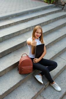 Uczennica siedzi na schodach kciuki w górę