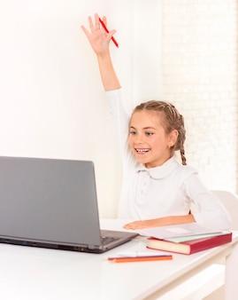 Uczennica siedzi przy laptopie i wyciąga rękę do góry