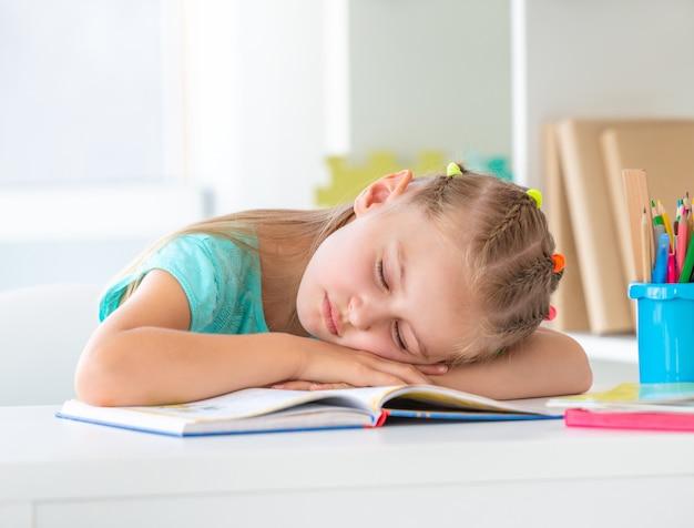 Uczennica śpi na otwartej książce