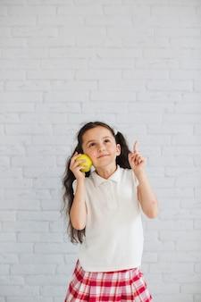 Uczennica stoi gospodarstwa jabłko skierowane w górę