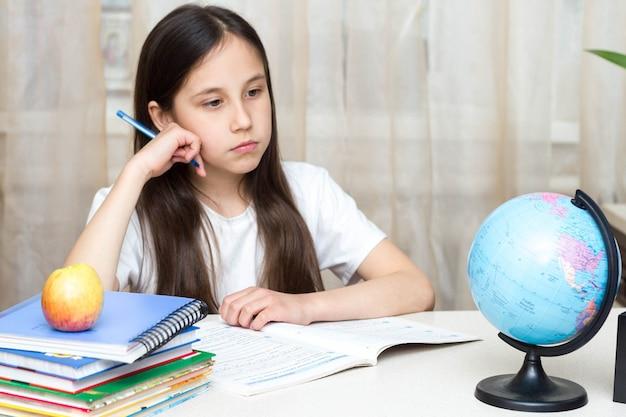 Uczennica studiuje w domu, odrabia pracę domową, siedząc przy stole, studiując świat powrót do koncepcji szkoły