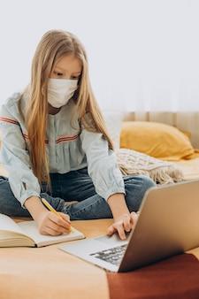 Uczennica studiuje w domu w masce, nauka na odległość
