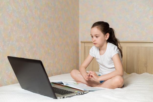 Uczennica studiuje w domu z cyfrowym pastylka laptopu notatnikiem i robi szkolnej pracie domowej na łóżku z szkolnymi książkami