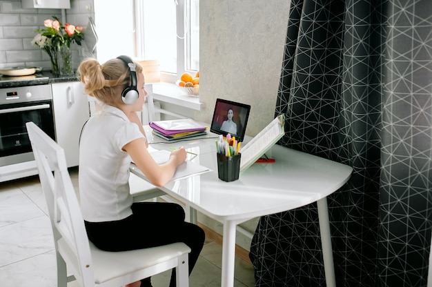 Uczennica szkoły młodzieżowej nosi słuchawki na konferencję i uczy się online ze zdalnym nauczycielem z domu. nastoletni uczeń za pomocą laptopa rozmawia przez kamerę internetową czat wideo lekcji nauki z nauczycielem odległości.