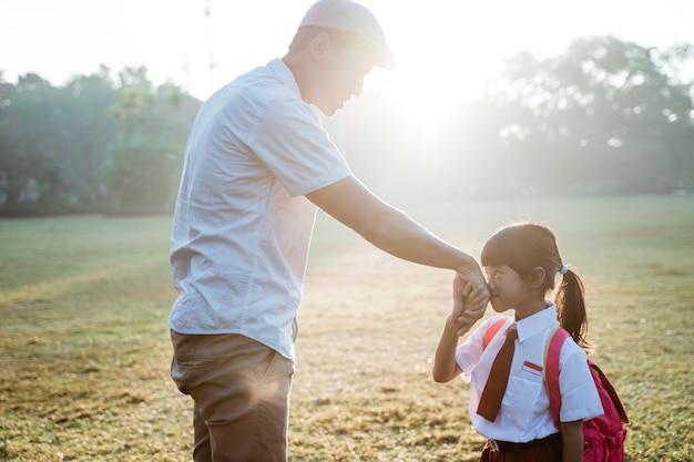 Uczennica szkoły podstawowej całuje rękę ojca, kiedy idzie do szkoły