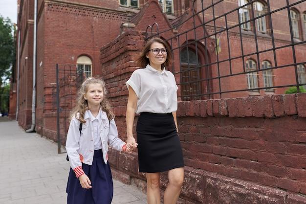 Uczennica szkoły podstawowej chodzenie z mamą trzymając się za ręce, rozmawiając z rodzicem i dzieckiem w drodze do szkoły. początek nauki, powrót do szkoły