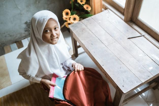 Uczennica szkoły podstawowej z indonezji przygotowująca książkę w domu przed pójściem do szkoły rano