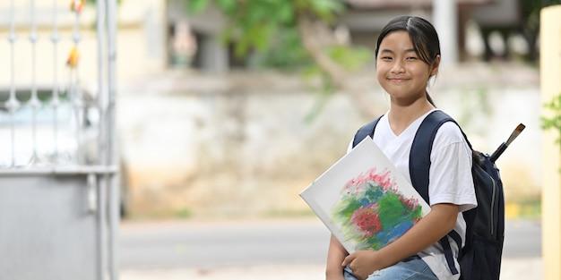 Uczennica trzyma sprzęt malarski i nosi torbę szkolną, stojąc i czekając na autobus szkolny.