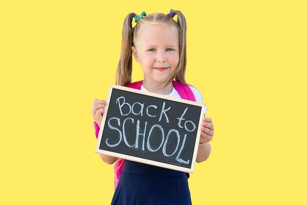 """Uczennica trzyma w rękach tabliczkę z napisem """"powrót do szkoły"""". izolować na żółtym tle"""