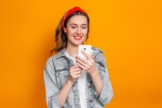 Uczennica ubrana w dżinsową kurtkę i chustkę patrzy na ekran telefonu komórkowego, czyta wiadomość, wiadomości i uśmiecha się na pomarańczowej ścianie. koncepcja edukacji online